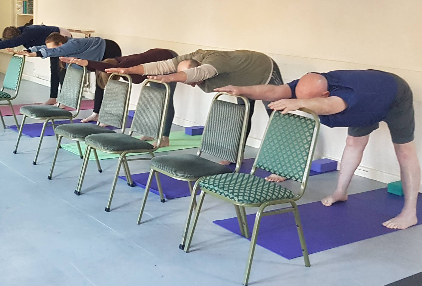students in half uttanasana with chair-1400w